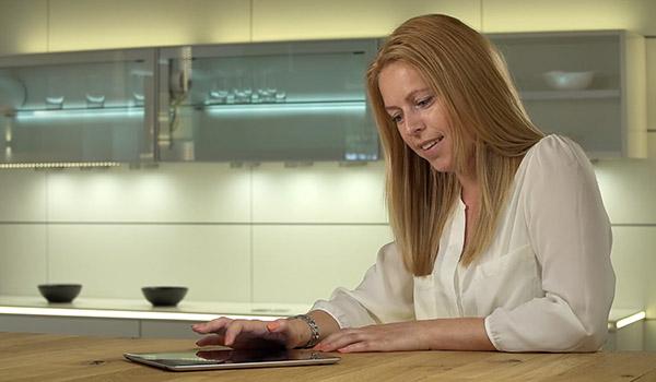 Frau an Tisch steuert Beleuchtung mit Tablet