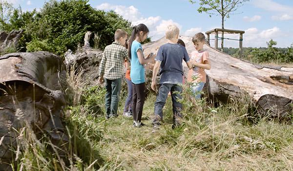 Kinder stehen mit Dosentelefon im Kreis
